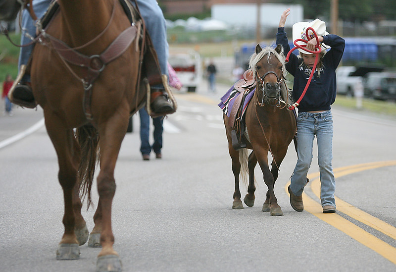 Jessica Tuxhorn, 9, loses control of her hat while walking her miniature horse, Gabe, before the parade starts.  Tanner Taylor rides Dolly next to her.