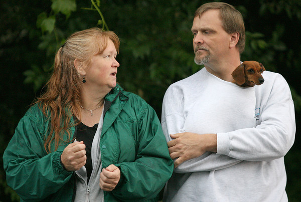Peggy Scheck talks with her husband, Stefan Martensson, while their dog, Emma, stays warm in his sweatshirt.