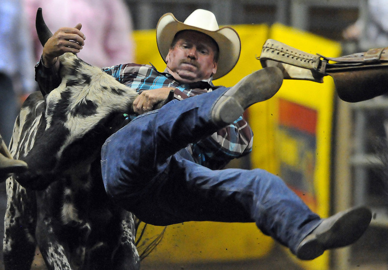 Kenny Johnson of Keenesburg goes airborne on his attempt to wrestle a steer on Tuesday at the PRCA Rodeo at the Dale Weist Arena at The Ranch.