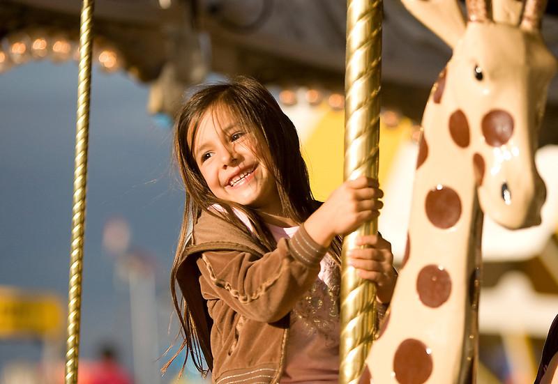Isabel Scadden, 6, from Aurora, rides a giraffe on the merry-go-round.
