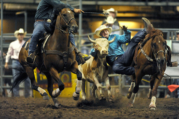 Wade Sumpter tackles his steer during the PRCA Rodeo at the Budweiser Event Center in Loveland on Monday. During the event the cowboy jumps from his horse on to a running steer and attemps to pin it on the ground as fast as possible. Sumpter was one of the top contenders of the evening.