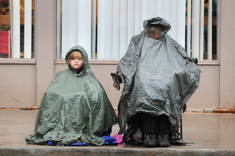 Dave Rhodes, right, gets a little reading done under his poncho as he and his daughter Dorothy, 6, wait out the rain before the start of the Larimer County Fair Parade on Wednesday evening.