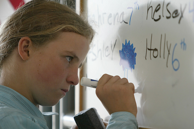 Sydney White, 11, from Masonville, draws a blue ribbon on a dry erase board.