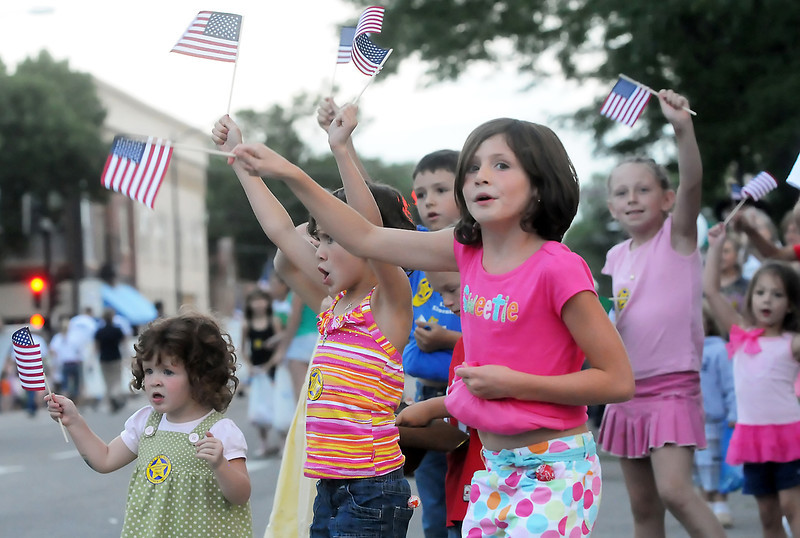 Youngsters cheer and wave while watching the Larimer County Fair parade on Wednesday, Aug. 4, 2010 in downtown Loveland. Front from left are Loveland residents Emma Lines, 2, Kassie Lines, 6, and Taylor Lines, 7.