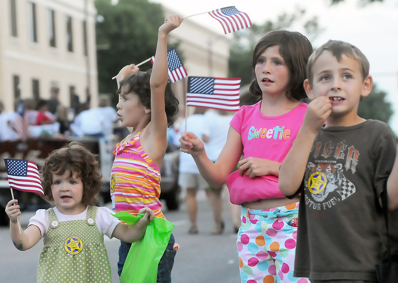 Youngsters cheer and wave while watching the Larimer County Fair parade on Wednesday, Aug. 4, 2010 in downtown Loveland. From left are Loveland residents Emma Lines, 2, Kassie Lines, 6, and Taylor Lines, 7, and Garrett Morali, 7, of Berthoud.
