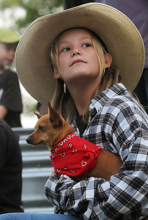 Twelve-year-old Robyn Hall of Livermore holds onto her dog, Zena, while riding atop the Livermore Wranglers 4-H Club float during the Larimer County Fair parade on Wednesday, Aug. 4, 2010 in downtown Loveland.