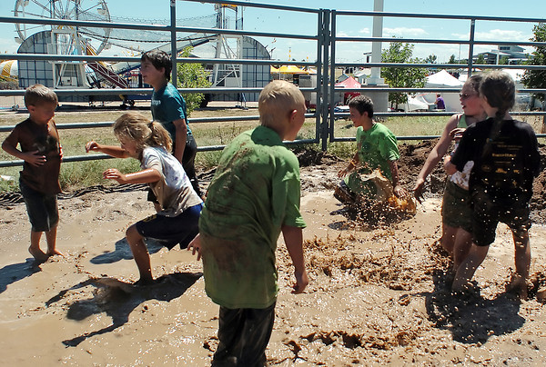 Youngsters play in a mud puddle during Wild and Crazy Kids Day as part of the Larimer County Fair on Tuesday at The Ranch.
