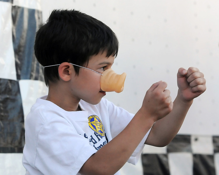 Six-year-old Max Cherkauer of Fort Collins wears a novelty pig nose he won while watching the Ham Bone Express pig races Friday at The Ranch during the Larimer County Fair.