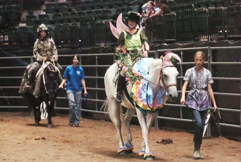 Eleven-year-old Kaley Kearns is dressed as a pixie as she sits atop a horse being lead around the arena by Alicia Burch, 13, right, during the costume competition of the Freedom Horse Therapeutic Riding Show on Friday at the Budweiser Events Center. At left is Besa Haise, 16, dressed as G.I. Jane with Taylor King, 17, walking alongside.