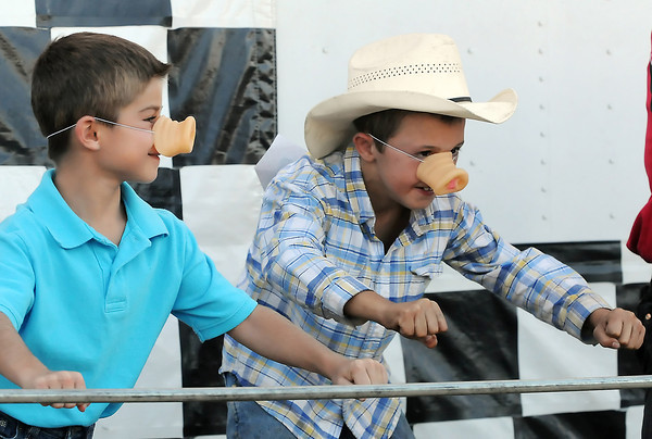 Longmont resident Jackson Mill, 8, left, and Will Thompson, 7, of Fort Collins ham it up and dance for the crowd while wearing pig noses they won while watching the Ham Bone Express pig races Friday at The Ranch.