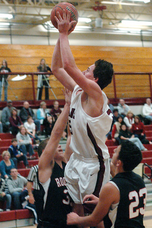 Berthoud High School senior Graham Shaw goes up for a shot between Roosevelt defenders Vince Pinezich, left, and Sam Hardy in the second quarter of their game on Friday, Dec. 18, 2009 at BHS. Berthoud won, 63-53.