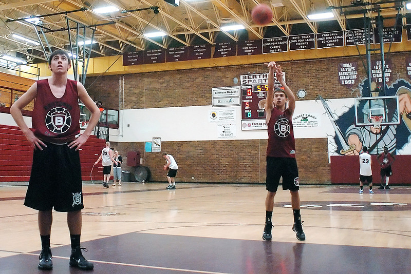 Berthoud High School sophomore Greg Hutchins, left, and senior Jeff Carlson shoot free throw with teammates during a drill at practice on Monday.