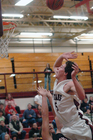 Berthoud High School senior Graham Shaw goes up for a shot over Roosevelt defender Vince Pinezich in the second quarter of their game on Friday, Dec. 18, 2009 at BHS. Berthoud won, 63-53.