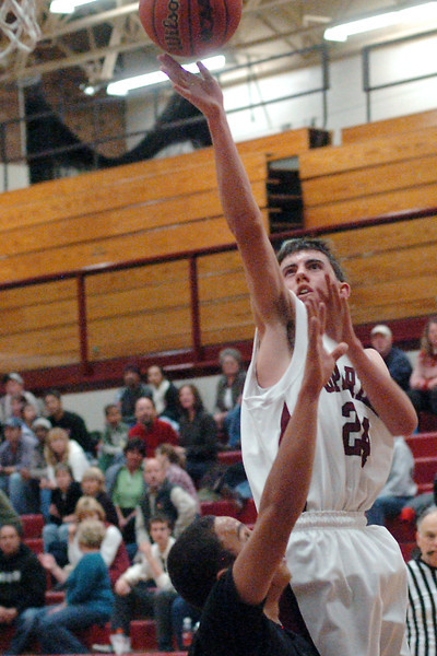 Berthoud High School sophomore Greg Hutchins lays the ball up over Roosevelt's Angelo Villamil in the third quarter of their game on Friday, Dec. 18, 2009 at BHS. The Spartans won, 63-53.
