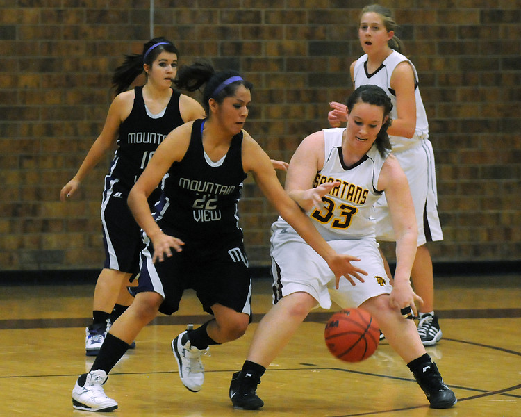 Mountain View High School's Nekisha Gonzales (22) steals the ball from Berthoud's Tonya Bezanson while Tamika Bjork, back left, and Lindsey Loberg look on in the on third quarter of their game on Tuesday, Dec. 7, 2010 at BHS. Mountain View won, 46-27.