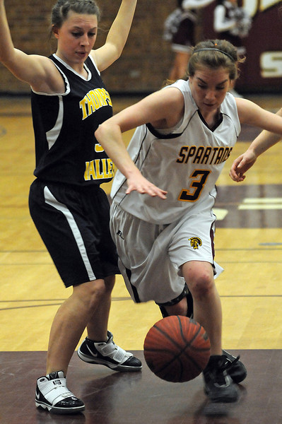 Berthoud High School junior Megan McGinn, right, tries to maintain control of the ball as she drives past sophomore Lauren Mickelson of Thompson Valley High School during the second quarter of Thursday night's game at Berthoud High School.
