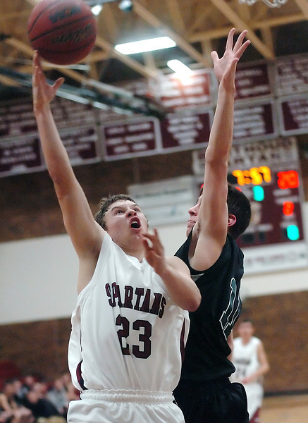 Berthoud High School sophomore Zach Ruebesam takes a shot over Fossil Ridge's Cody McCoy in the third quarter of their game Tuesday at BHS.