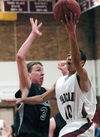Berthoud High School freshman Alex Santos goes up for a shot in front of Fossil Ridge's Ben Petersen in the second quarter of their game Tuesday at BHS.