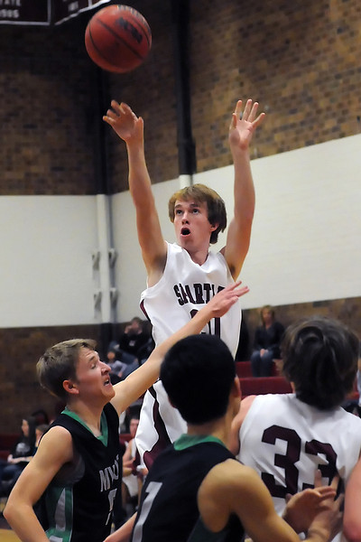 Berthoud High School junior Jesse Queen, back, puts up a shot over Niwot's Sam Forrer, left, in the second quarter of their game on Saturday, Jan. 29, 2011 at BHS.