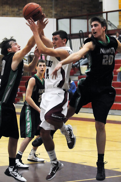 Berthoud High School junior Gregory Hutchins, center, grabs a rebound in the lane amidst Niwot players Andy Wegleitner, left, Cody Heimann, back, and Henry Sebesta in the third quarter Saturday night at BHS.