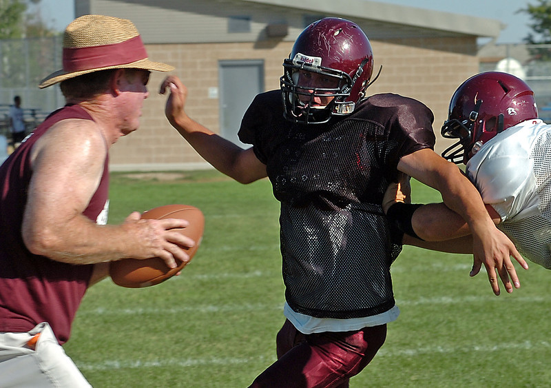 Berthoud High School football offensive lineman Zack Smith practices Tuesday at the school as defensive lineman coach Rusty Mathena, left, directs the players.