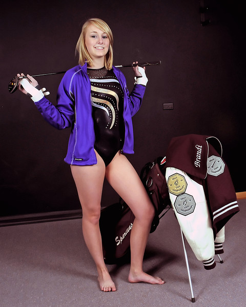 Berthoud High School junior and 3-sport athlete Brandi Peter poses Saturday while wearing her Thompson Valley gymnastics outfit and Mountain View diving jacket while standing next to her golf clubs with her Berthoud letter jacked draped over the clubs.