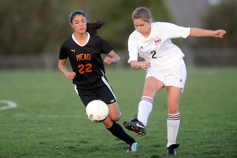 Berthoud High School sophomore Sara Sterck, right, passes the ball in front of Mead's Morgan Lu in the first half of their game Tuesday, April 24, 2012 at Marr Field.