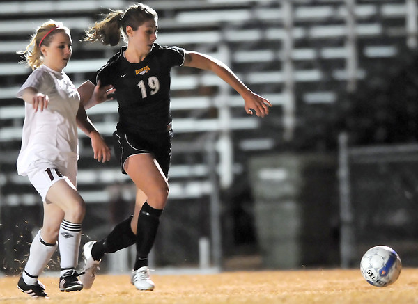 Thompson Valley High School senior Emma Howard, right, and Berthoud's Kara Lind track down the ball in the second half of their game Wednesday, March 17, 2010 at Marr Field in Berthoud. Howard scored two goals in the Eagles' 5-0 win over the Spartans.