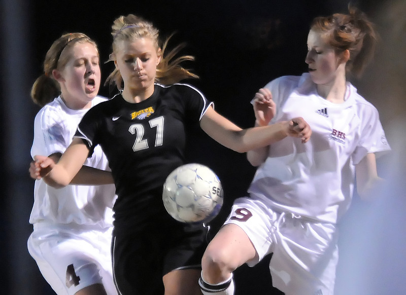 Thompson Valley High School senior Sydney Paulsen, center, battles for the ball with Berthoud's Lindsey Loberg, left, and Sydney Cooke in the first half of their game Wednesday, March 17, 2010 at Marr Field in Berthoud. Paulsen scored two goals in the Eagles' 5-0 win over the Spartans.