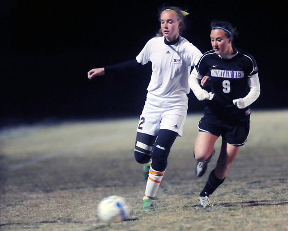 Berthoud High School sophomore Megan Loberg, left, and Mountain View senior Kayla Grimes track down the ball in the second half of their match Thursday night at Marr Field in Berthoud. The Mountain Lions won, 4-0.
