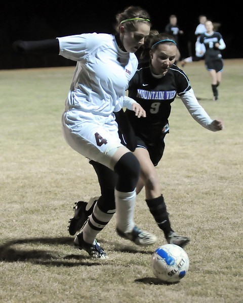 Berthoud High School's Amy Loberg, left, and Mountain View's Kayla Grimes battle for the ball in the second half of their match Thursday night at Marr Field in Berthoud. The Mountain Lions won, 4-0.