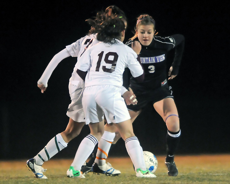 Mountain View High School Rikelle Berry, right, goes against Berthoud's Rhya Stoesz (19) and Cherokee Walker in the second half of their match Thursday night at Marr Field in Berthoud. The Mountian Lions won, 4-0.