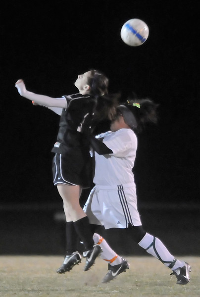 Mountain View High School's Emily McFeron, left, and Berthoud's Amy Taylor go up for the ball in the second half of their match Thursday night at Marr Field in Berthoud. The Mountain Lions won, 4-0.