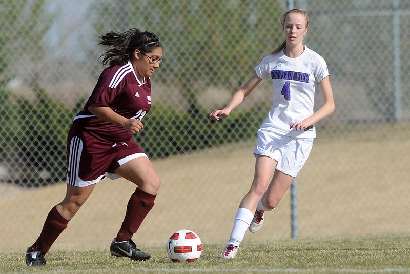 Berthoud High School's Esther Martinez, left, and Mountain View's Jessie Rollstin chase down the ball in the first half of their game Wednesday, March 28, 2012 at MVHS.