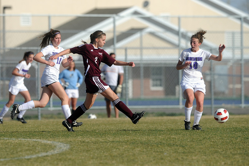 Berthoud High School's Sara Sterck, middle, passes the ball in between Mountain View's Hallie Stolte, left, and MaKenzie Ross in the first half of their game Wednesday, March 28, 2012 at MVHS.