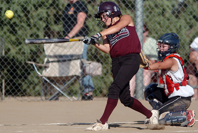 Berthoud High School junior Ashley Prescott hits a single as Roosevelt catcher Morgan Devine looks on in the bottom of the fourth inning of their game Tuesday at BHS.
