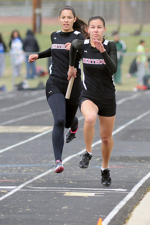 Berthoud High School junior Ally Kales, right, sprints away from teammate Mimi Garcia after receiving the baton while competing in a heat of the 800-meter relay during the Max Marr Invitational on Saturday, April 13, 2013 at BHS.