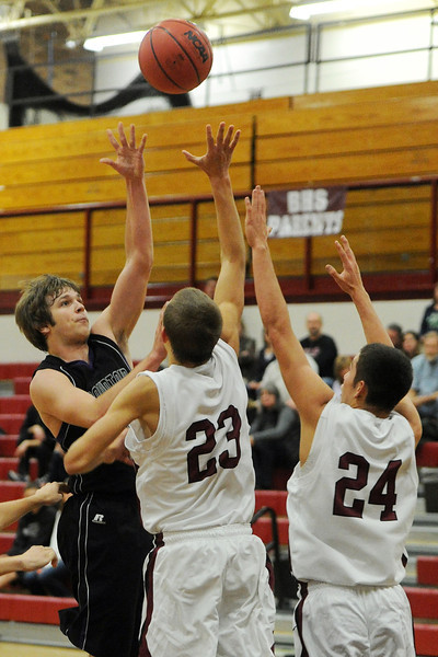 Mountain View High School's Hunter Porterfield, left, puts up a shot over Berthoud's Robert Colestock (23) and Ryan Vasquez (24) in the second quarter of their game on Wednesday, Nov. 28, 2012 at BHS.