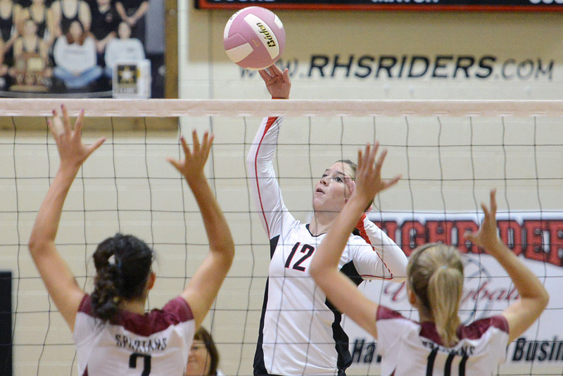 Roosevelt High School's Breanne Hankins (12) hits the ball against Berthoud's Mimi Garcia, left, and Hannah Atkinson during set three of their match on Tuesday, Oct. 9, 2012 at RHS. The RoughRiders won, 3-1.