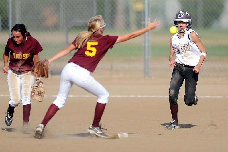 Berthoud High School's Samantha Kouns, right, advances to second base as Windsor second baseman Haley Anderson, middle, attempts to field the ball in the bottom of the second inning of  their game on Thursday, Sept. 20, 2012 at Bein Park.