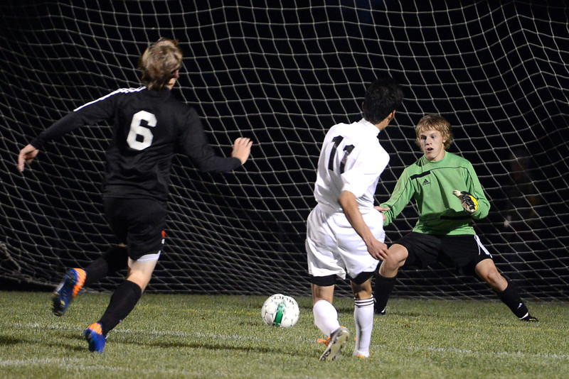 Berthoud High Schooljunior Daniel Beltran Ayala (11) scores a goal past Roosevelt goalie Alec Stewart and defender Tanner Hentges in the first half of their match on Wednesday, Sept. 12, 2012 at Marr Field.