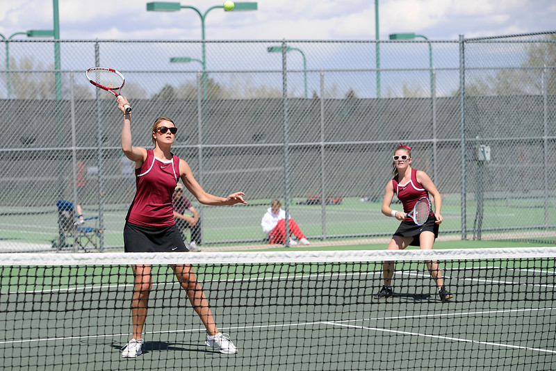 Berthoud High School's Elle Satterthwaite, left, returns a shot at the net while her No. 4 doubles partner Jamie Young looks on during their semi-final match against Weld Central for the Northern Colorado Invitational at Loveland High School.
