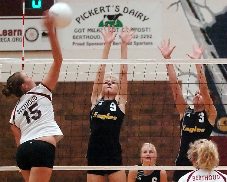 Berthoud High School sophomore Sara Nienaber (15) attempts a spike over Thompson Valley's Katie Ayres (9) and Lindsey Laws (3) while Clara Lundeen, back, and Clara Levy, right, look on in the first game of their match Friday at BHS. Thompson Valley won, 3-0.
