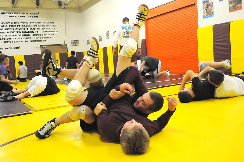 Berthoud High School junior Tylor Bethel, front, and senior Robbie Workman work on a drill together during wrestling practice on Wednesday at the school.