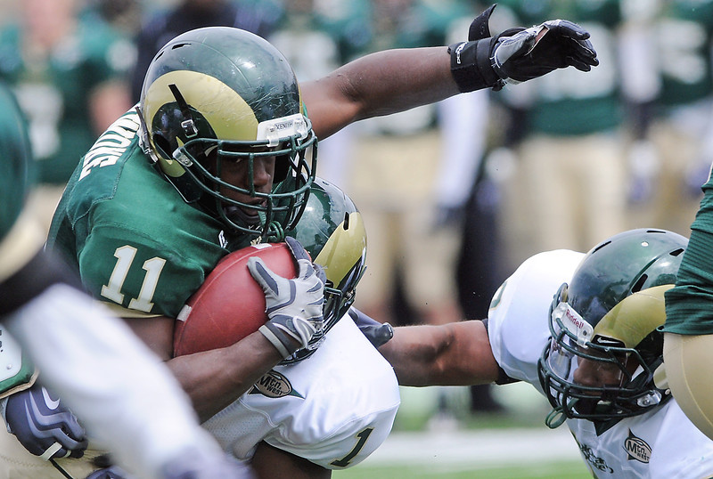 Colorado State University running back Chris Nwoke is tackled by safety Mike Orakpo (1) and defensive end Broderick Sargent during the Green and Gold game Saturday at Hughes Stadium in Fort Collins.