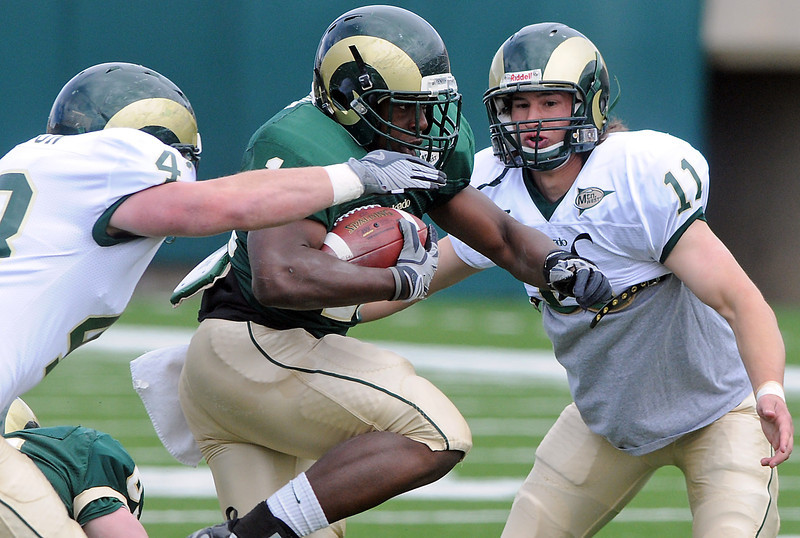 Colorado State University running back Chris Nwoke is pursued by defenders James Skelton, left, and Austin Gillmore during the Green and Gold game Saturday at Hughes Stadium in Fort Collins.