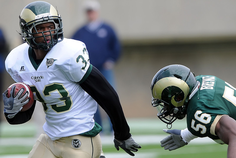 Colorado State University football running back Lou Greenwood, left, is pursued by linebacker Ricky Brewer during the team's Green and Gold game on Saturday, April 24, 2010 at Hughes Stadiium in Fort Collins.