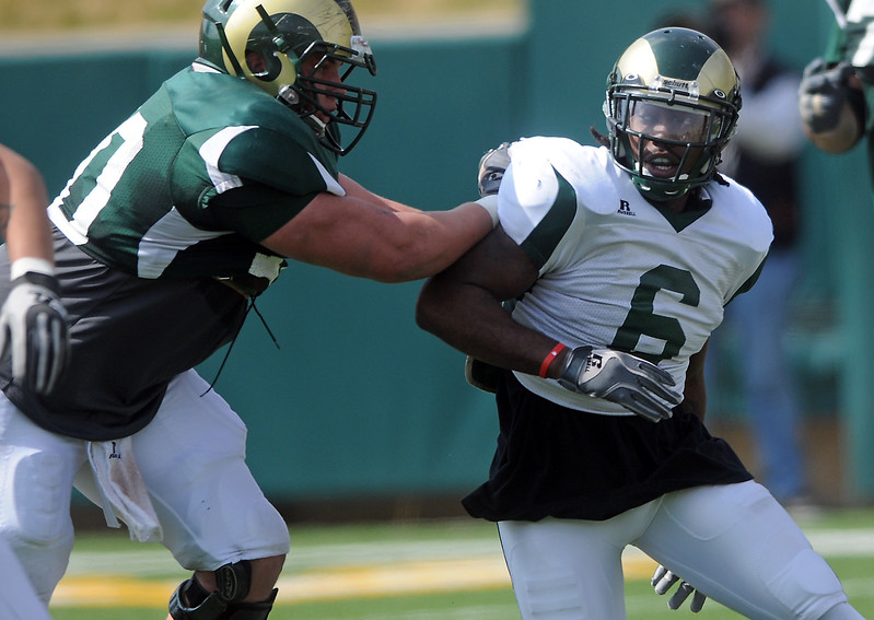 Colorado State University linebacker Mychal Sisson, right, fights around a block by lineman Weston Richburg during the team's spring football game Saturday, April 9, 2011 at Hughes Stadium in Fort Collins, Colo.