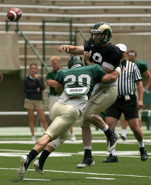 Colorado State University quarterback, Grant Stucker, passes the ball just in time to avoid a sack by defensiveback Klint Kubiak during a scrimmage Saturday at Lubick Field at Hughes Stadium in Fort Collins.