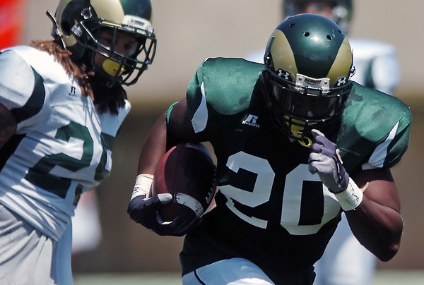 Colorado State University running back Raymond Carter makes a carry in front of safety Travis Ford during a scrimmage on Saturday, Aug. 14, 2010 at Hughes Stadium in Fort Collins.